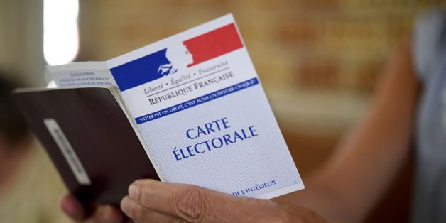 A woman holds a electoral card at a polling station in Carhaix-Plouguer, western France, during the second round of the French parliamentary elections (elections legislatives in French) on June 18, 2017. / AFP PHOTO / Fred TANNEAU        (Photo credit should read FRED TANNEAU/AFP/Getty Images)