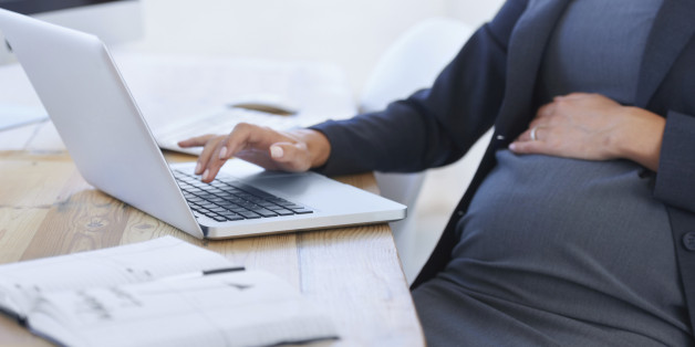 Cropped image of a pregnant businesswoman working on her laptop in the office