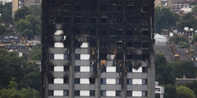 Unburned lower floors with untouched cladding in place are seen with the burnt out upper floors of the Grenfell Tower block in North Kensington, west London, on June 18, 2017. The presumed death toll from the London tower block inferno jumped to 58 on Saturday as embattled Prime Minister Theresa May, accused of misreading the growing anger over the tragedy, pledged action after meeting survivors desperately seeking answers. / AFP PHOTO / Tolga AKMEN        (Photo credit should read TOLGA AKMEN/A