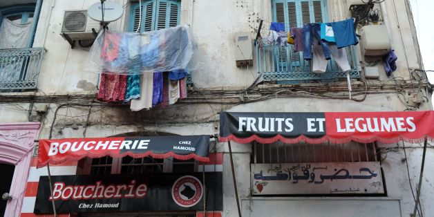 Clothes hang above shops bearing the colours of the Union Sportive Medina d'Alger (USMA) football club in the Soustara neighbourhood in the old part of Algiers known as the 'Casbah', which is historically known to be predominantly supporting USMA, in Algiers on October 11, 2016, two days ahead of the 100th derby match against their rival Mouloudia Club d'Alger (MCA).