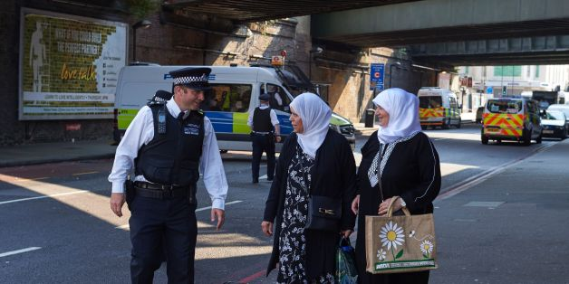 A police officer speaks to local residents at a police cordon, close to the scene of a van attack in Finsbury Park, north London on June 19, 2017.