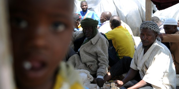 Illegal migrants from Niger sit next to their tents on May 14, 2014 after settling, some of them for more than one year, near the fruit market in the Algerian town of Boufarik, 35 km south of the capital Algiers in the Blida province. The Sahel-Sahara region has been plagued by jihadist violence and severe food shortages. Some Algerian newspapers articles have recently shown signs of racism against African migrants arriving in the country to flee violence and poverty back home.  AFP PHOTO/FAROUK