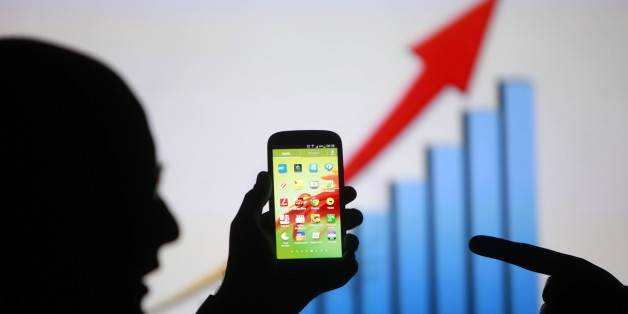 Men are silhouetted against a video screen as they pose with a Samsung Galaxy S3 smartphone in this photo illustration taken in the central Bosnian town of Zenica, May 17, 2013. Overtaking Apple Inc as the world's leading maker of smartphones has stretched Samsung Electronics Co's in-house supply lines, and the South Korean firm is now courting some of its rival's main parts suppliers as they jostle to rule the $253 billion smartphone market.  REUTERS/Dado Ruvic (BOSNIA AND HERZEGOVINA - Tags: B