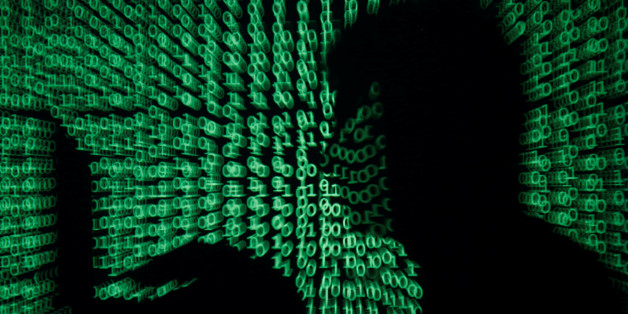A man holds a laptop computer as cyber code is projected on him in this illustration picture taken on May 13, 2017. Capitalizing on spying tools believed to have been developed by the U.S. National Security Agency, hackers staged a cyber assault with a self-spreading malware that has infected tens of thousands of computers in nearly 100 countries. REUTERS/Kacper Pempel/Illustration