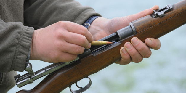 Close-up of a hunter loading his rifle.