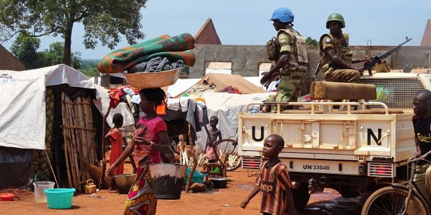 A woman and a child walk past UN peacekeepers from Gabon patrolling the Central African Republic town of Bria on June 12, 2017.