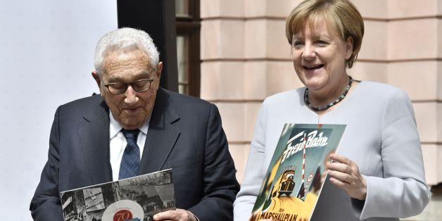 German Chancellor Angela Merkel and former US Secretary of State Henry Kissinger hold a recording of George Marshall on a vinyl record they received as a gift for participating in a conference titled '70 Years of Marshall Plan' organised by the German Marshall Funds of the United States at the Deutsches Historisches Museum in Berlin on June 21, 2017. / AFP PHOTO / John MACDOUGALL        (Photo credit should read JOHN MACDOUGALL/AFP/Getty Images)