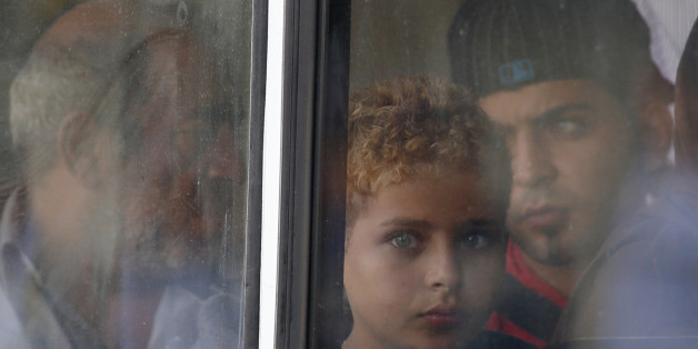 A rescued migrant child looks out of the window of a police bus after arriving at the Armed Forces of Malta Maritime Squadron base at Haywharf in Valletta's Marsamxett Harbour October 12, 2013. Dozens of people died on Friday when a boat carrying around 250 migrants capsized between Sicily and Tunisia, in the second such shipwreck this month, the Italian coastguard said. 147 survivors, believed to all be Syrians, arrived in Malta on Saturday morning, according to local media.