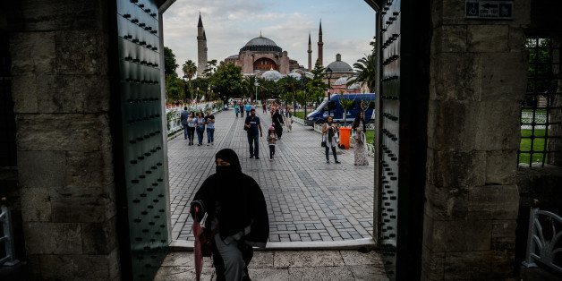 TOPSHOT - A woman walks through a gate of the Blue mosque square before breaking time as Hagia Sofia is seen on the background on June 6, 2016 in Istanbul, during the first day of the holy month of Ramadan. 