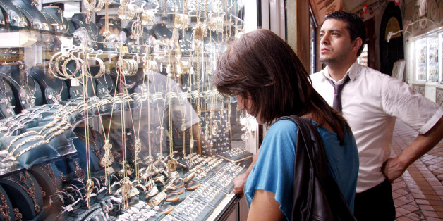 A Tunisian couple looks at the display in a jewelry shop window in the souk of Medina on September 14, 2011 in Tunis. Despite the recession in Tunisia following the revolution, and high gold prices worldwide, Tunisian jewelers still enjoy brisk trade thanks to the tradition of the wedding trousseau. AFP PHOTO/ SALAH HABIBI (Photo credit should read SALAH HABIBI/AFP/Getty Images)