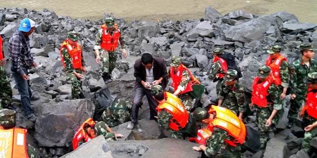CORRECTION - Chinese military police and rescue workers are seen at the site of a landslide in in Xinmo village, Diexi town of Maoxian county, Sichuan province on June 24, 2017. Around 100 people are feared buried after a landslide smashed through their village in southwest China's Sichuan Province early Saturday, local officials said, as they launched an emergency rescue operation. / AFP PHOTO / STR / China OUT / The erroneous mention[s] appearing in the metadata of this photo by STR has been m