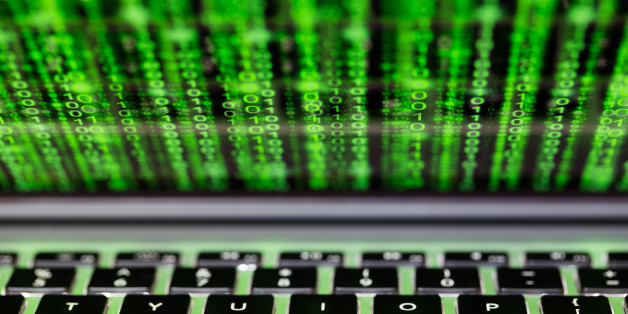 Laptop screen and keyboard with green binary matrix code closeup cybersecurity concept