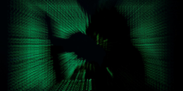 A  hooded man holds laptop computer as cyber code is projected on him in this illustration picture taken on May 13, 2017. Capitalizing on spying tools believed to have been developed by the U.S. National Security Agency, hackers staged a cyber assault with a self-spreading malware that has infected tens of thousands of computers in nearly 100 countries. REUTERS/Kacper Pempel/Illustration