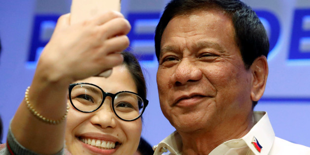 A journalist takes a selfie with Philippine President Rodrigo Duterte after a news conference in Manila, Philippines April 29, 2017.  REUTERS/Erik De Castro