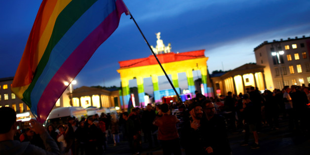 People stand in front of Brandenburg gate, lit up in support of the victims killed in an Orlando gay nightclub, in Berlin, Germany, June 18, 2016. REUTERS/Hannibal Hanschke