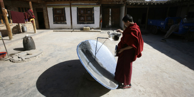 Ein Mönch in Tongren, Qinghai kocht sein Mittagessen auf einem solarbetriebenen Ofen