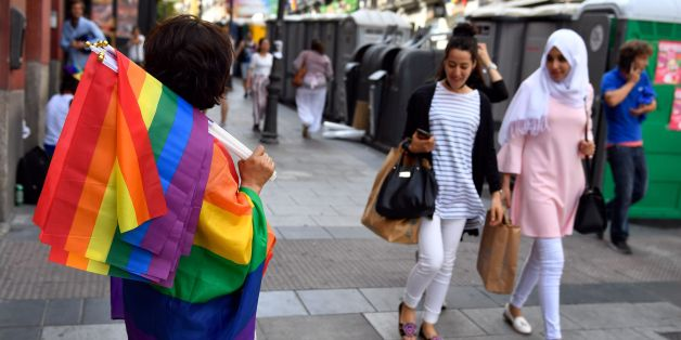 Two women walk past a street vendor selling rainbow flags in Madrid's Chueca district on June 28, 2017 before the official proclamation of the WolrdPride 2017.Some three million revellers are expected in the Spanish capital as the city hosts WorldPride 2017, one of the biggest and most important celebrations of lesbian, gay, transsexual and bisexual rights. / AFP PHOTO / GERARD JULIEN        (Photo credit should read GERARD JULIEN/AFP/Getty Images)