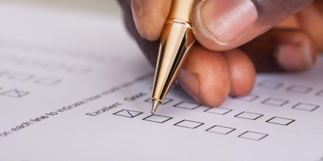 Close-up Of Businessman Filling Customer Survey Form