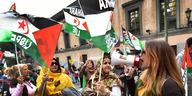 Activists for the independence of the Western Sahara wave flags  during an annual protest organised by the state coordinator of associations of solidarity with the Sahara in Madrid on November 11, 2016 marking the 4th anniversary of the tripartite Madrid agreements demonstrators deem illegal. The Western Sahara is a territory bordered by Morocco and Algeria and disputed by Spain and Morocco who both claiming sovereignty. / AFP / GERARD JULIEN        (Photo credit should read GERARD JULIEN/AFP/Ge