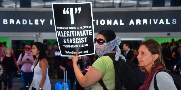 Activists hold placards outside the International Arrivals section at Los Angeles International Airport on June 29, 2017, protesting President Donald Trump's ban temporarily barring entry into the US from Libya, Iran, Somalia, Sudan, Syria and Yemen goes into effect.The ban prevents the issuance of visas to travelers from the sixcountries for 90 days and places the refugee-entry program on hold for 120 days. / AFP PHOTO / FREDERIC J. BROWN        (Photo credit should read FREDERIC J. BROWN/AFP/G