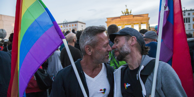 Two men kiss in front of Brandenburg Gate during an evening vigil in Berlin, Germany on June 18, 2016. Mourners gathered to commemorate the victims of a shooting at the gay nightclub 'Pulse' in Orlando, Florida, happened nearly a week earlier, in front of Brandenburg Gate enlightened with the LGBT rainbow colours. Fifty people died in the massacre and about fiftythree injured. (Photo by Emmanuele Contini/NurPhoto via Getty Images)