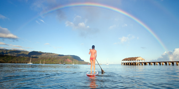 Stand up paddle board in hanalei bay with rainbow in Kauai, Hawaii, USA