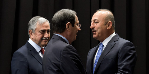 Turkish Foreign Minister Mevlut Cavusoglu (R) greets Greek Cypriot President Nicos Anastasiades (C) next to Turkish Cypriot Leader Mustafa Akinci (L) during peace talks in the Swiss resort of Crans-Montana on June 30, 2017. More than 40 years after Turkish troops invaded northern Cyprus, the presence of tens of thousands of soldiers on the Mediterranean island still looms large over make-or-break peace negotiations this week. / AFP PHOTO / Fabrice COFFRINI        (Photo credit should read FABRICE COFFRINI/AFP/Getty Images)