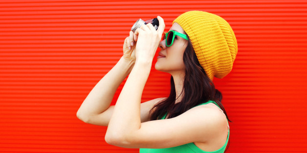 Fashion pretty cool girl wearing a colorful clothes with old retro camera shooting in the city