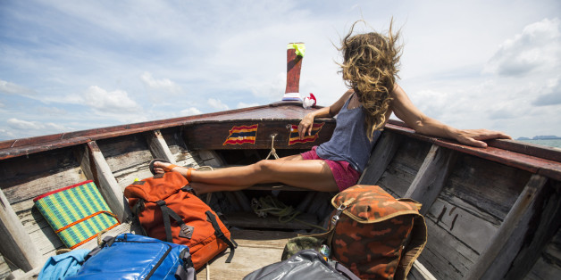 A woman with multiple bags traveling on a long-tail boat in Thailand.