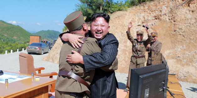 TOPSHOT - This picture taken on July 4, 2017 and released by North Korea's official Korean Central News Agency (KCNA) on July 5, 2017 shows North Korean leader Kim Jong-Un (C) celebrating the successful test-fire of the intercontinental ballistic missile Hwasong-14 at an undisclosed location.