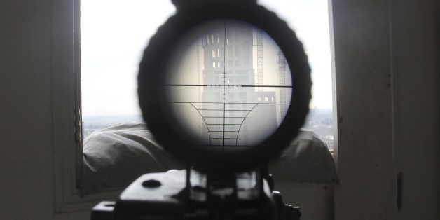 A view seen through the scope of a weapon belonging to a sniper and rebel fighter shows a building where forces loyal to Syria's President Bashar al-Assad are stationed, as seen from a rebel-controlled area in the northwestern Homs district of Al Waer February 18, 2015. Picture taken February 18. REUTERS/Stringer  (SYRIA - Tags: MILITARY POLITICS CIVIL UNREST CONFLICT TPX IMAGES OF THE DAY)