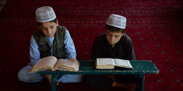 TOPSHOT - Afghan children read the Koran at a madrasa during the holy month of Ramadan in Ghazni on June 13, 2017.Muslims throughout the world are marking the month of Ramadan, the holiest month in the Islamic calendar during which devotees fast from dawn until dusk. / AFP PHOTO / ZAKERIA HASHIMI        (Photo credit should read ZAKERIA HASHIMI/AFP/Getty Images)