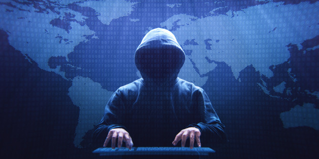 Anonymous computer hacker sitting in front of a virtual screen.