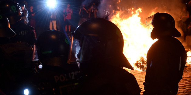 Police officers walk in front of a fire after the 'Welcome to Hell' rally against the G20 summit in Hamburg, northern Germany on July 6, 2017. 