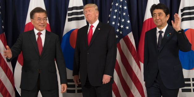US President Donald Trump (C), Japanese Prime Minister Shinzo Abe (R) and South Korean President Moon Jae-in pose for photos before attending the Northeast Asia Security Dinner at the US Consulate General Hamburg on the sidelines of the G20 Summit in Hamburg, Germany, July 6, 2017.Leaders of the world's top economies will gather from July 7 to 8, 2017 in Germany for likely the stormiest G20 summit in years, with disagreements ranging from wars to climate change and global trade. / AFP PHOTO / SA