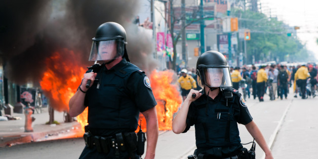 Toronto, Canada - June 26, 2010: A male and female police officer standing in front of a burning police car.  Taken during the G20 riots in Toronto, Canada on June 26th, 2010.  Several police cars were lit on fire in the city's downtown core in protest of the G20/G8 summits.