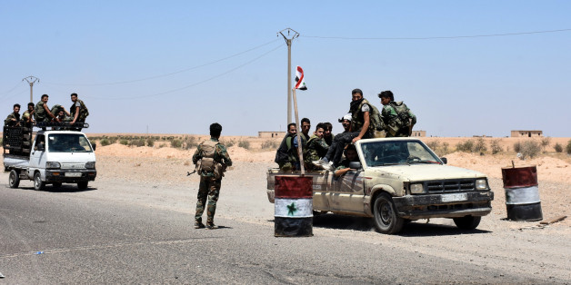 A picture taken on July 8, 2017 shows members of the Syrian pro-government forces riding in vehicles on the road near the Syrian village of Hanna Safar, on the western outskirts of Raqa province. / AFP PHOTO / George OURFALIAN        (Photo credit should read GEORGE OURFALIAN/AFP/Getty Images)