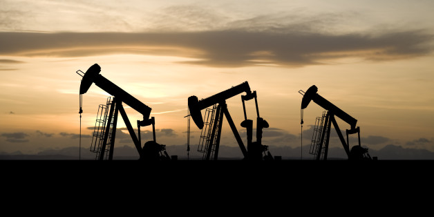 Three oil and gas industry derricks work as the sun sets behind them.