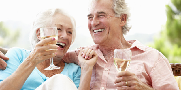 Senior Couple Sitting On Outdoor Seat Together Drinking Wine Laughing