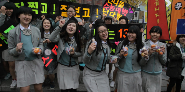 SEOUL, SOUTH KOREA - NOVEMBER 08:  South Korean high school girls cheer for their senior classmates taking the College Scholastic Ability Test on November 8, 2012 in Seoul, South Korea. More than 660,000 high school seniors and graduates sit for the examinations at 1,100 test centers across the country, where academic records are all important. Success in the exam, one of the most rigourous standardized tests in the world, enables students to study at Korea's top universities.  (Photo by Chung S