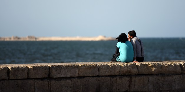 An Egyptian couple sits on a wall by the sea on September 12, 2015 in the Egyptian port city of Alexandria. AFP PHOTO / MOHAMED EL-SHAHED        (Photo credit should read MOHAMED EL-SHAHED/AFP/Getty Images)