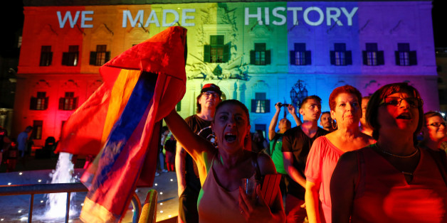 People celebrate in front of the rainbow-colour lit Auberge de Castille, the office of Prime Minister Joseph Muscat, after the Maltese parliament voted to legalise same-sex marriage on the Roman Catholic Mediterranean island, in Valletta, Malta, July 12, 2017.  REUTERS/Darrin Zammit Lupi