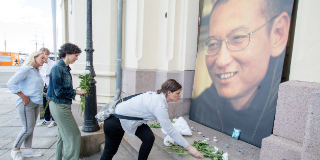 People place flowers and light candles in front a picture of late Nobel Peace Laureate Liu Xiaobo outside the Nobel Peace Center in Oslo, Norway July 13, 2017. NTB Scanpix/Audun Braastad via REUTERS ATTENTION EDITORS - THIS IMAGE WAS PROVIDED BY A THIRD PARTY. NORWAY OUT. NO COMMERCIAL OR EDITORIAL SALES IN NORWAY.      TPX IMAGES OF THE DAY