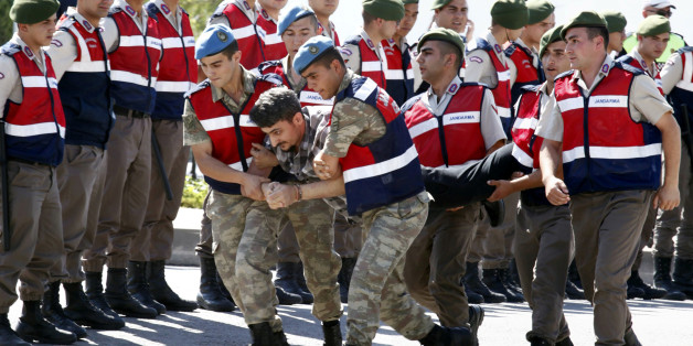 A soldier accused of attempting to assassinate Turkish President Tayyip Erdogan on the night of the failed July 15, 2016 coup is carried by gendarmes to the courthouse in Mugla, Turkey July 14, 2017. REUTERS/Kenan Gurbuz