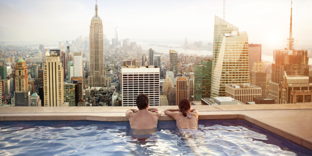 Couple relaxing in swimming pool on hotel rooftop