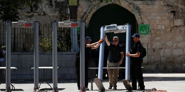 Israeli border policemen install metal detectors outside the Lion's Gate, a main entrance to Al-Aqsa mosque compound, in Jerusalem's Old City, on July 16, 2017, after security forces reopened the ultra-sensitive site, whose closure after a deadly attack earlier in the week sparked anger from Muslims and Jordan, the holy site's custodian. Three Arab Israeli assailants opened fire on Israeli police on July 14 in the Old City, killing two of them before fleeing to the nearby Haram al-Sharif compoun