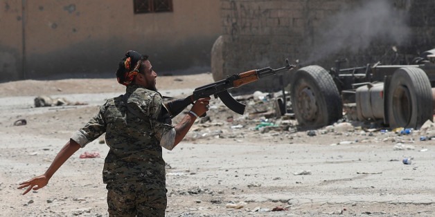 A Kurdish fighter from the People's Protection Units (YPG) fires his rifle at Islamic State militants as he runs across a street in Raqqa, Syria July 3, 2017. REUTERS/Goran Tomasevic