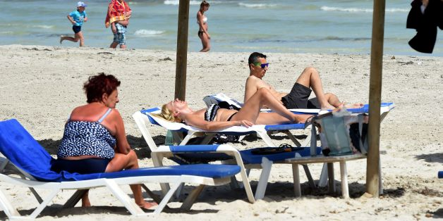 Tourists sit on the beach on the Tunisian resort island of Djerba on May 26, 2016.  / AFP / FETHI BELAID        (Photo credit should read FETHI BELAID/AFP/Getty Images)