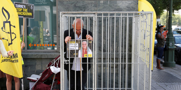 Amnesty International Belgium's Director Philippe Hensmans poses in a cage in front of the Turkish embassy in Brussels to protest against the detention of his Turkish counterpart Idil Eser, Belgium, July 10, 2017.  REUTERS/Francois Lenoir TPX IMAGES OF THE DAY