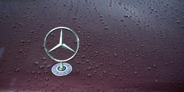 'Padua, Italy - July 6, 2011: Mercedes classical logo on a wet car hood. Mercedes-Benz, a division of Daimler AG, is a German manufacturer of automobiles, buses, coaches, and trucks. The name traces its origins to Daimler 1901 Mercedes and to Karl Benz 1886 Benz Patent Motorwagen, widely regarded as the first automobile. Mercedes today is synonymous with luxury, sportiness and technical reliability. Shot in a public parking.'